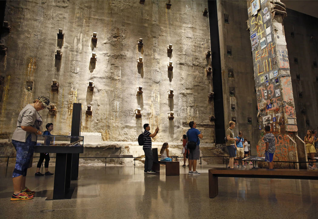 In this July 11, 2017 photo, visitors to the Foundation Hall at the National September 11 Memorial and Museum view the slurry wall, rear, and a beam from one of the World Trade towers, right, that ...