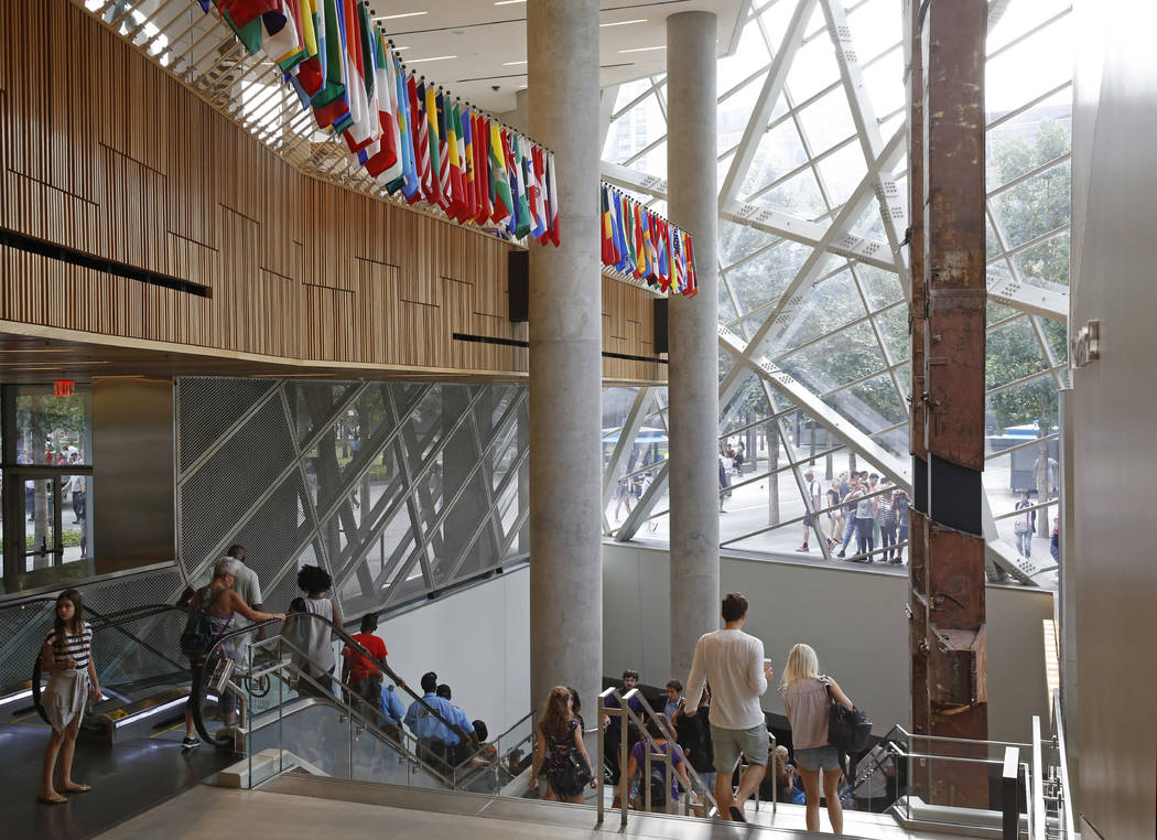 """In this July 11, 2017 photo, visitors make their way through the National September 11 Memorial and Museum in New York. Last winter the U.S. tourism industry worried about a """"Trump slump,"""" fearing ..."""
