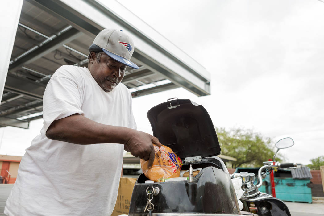 Garry Coleman situates his food to fit into his scooter during United States Department of Agriculture's food commodities distribution giveaway that occurs every other month at the Las Vegas Rescu ...