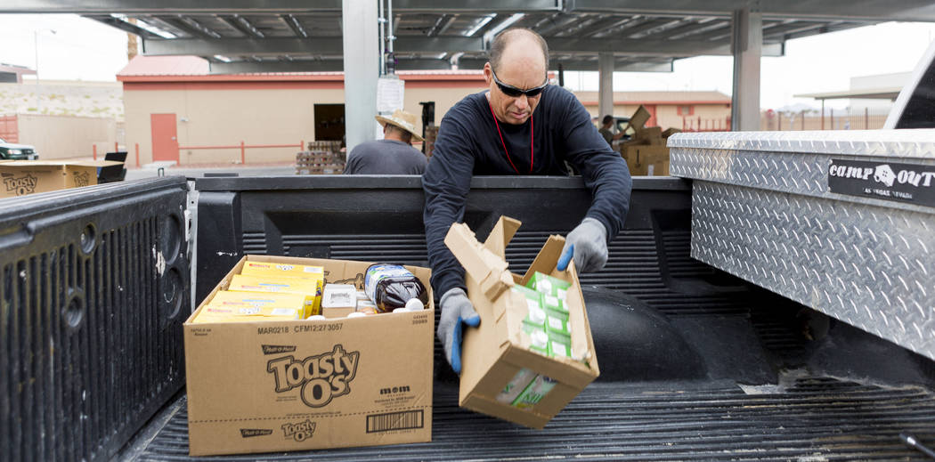 Work therapy participant Robert Edler loads a vehicle with food donations during the United States Department of Agriculture's food commodities distribution giveaway that occurs every other month  ...