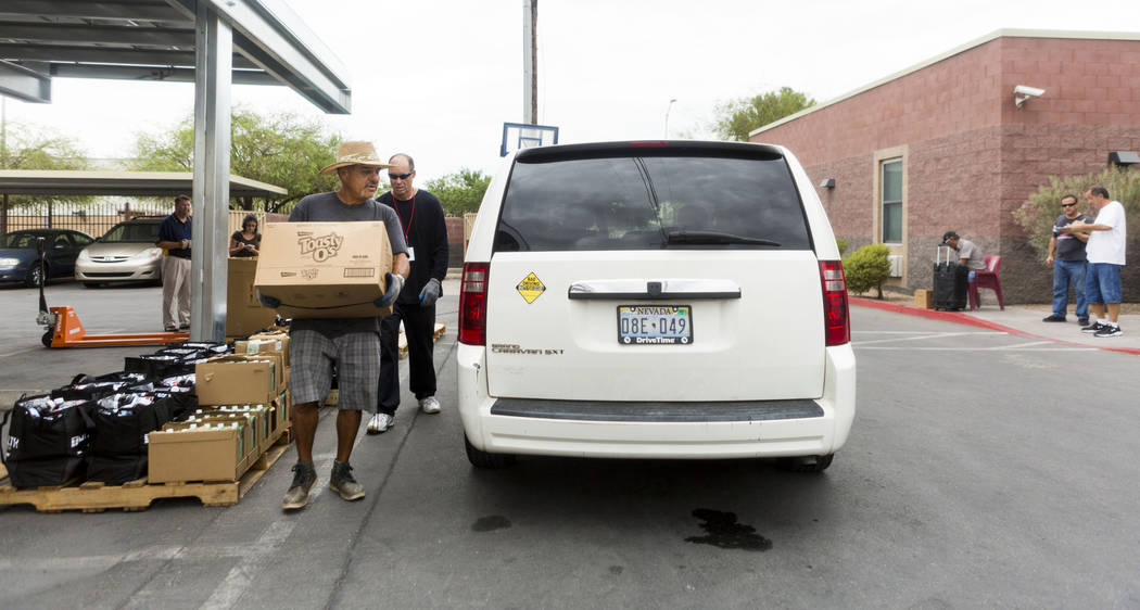 Work therapy participant Angelo Uribe loads a car with food during the United States Department of Agriculture's food commodities distribution giveaway that occurs every other month at the Las Veg ...