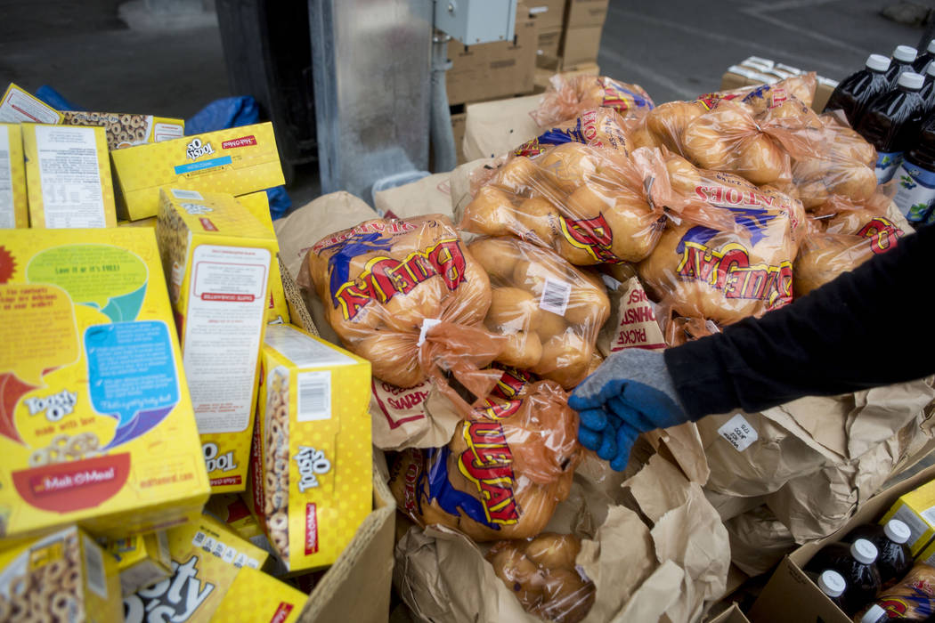 Work therapy participant Robert Edler prepares a box of food items to load into a car for a family during the United States Department of Agriculture's food commodities distribution giveaway that  ...