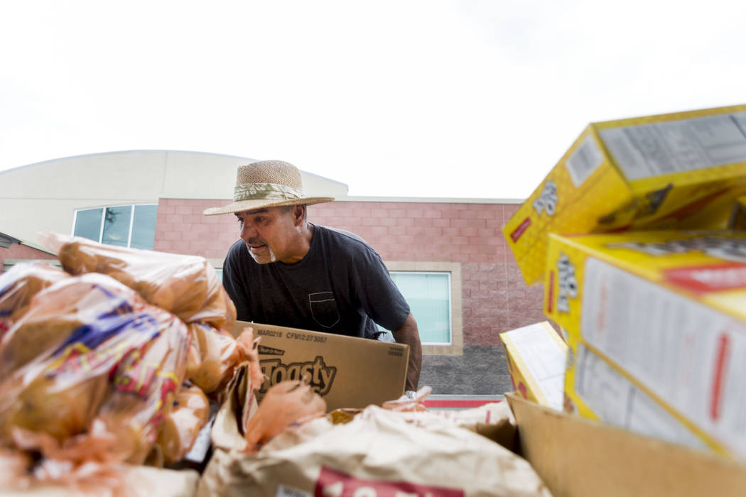 Work therapy participant Work therapy participant Angelo Uribe prepares a box of food items to load into a car for a family during the United States Department of Agriculture's food commodities di ...