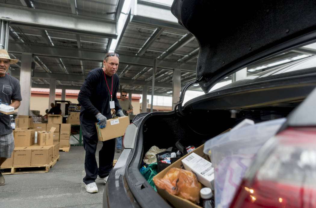 Work therapy participant Work therapy participant Robert Edler loads food items into a car for a family during the United States Department of Agriculture's food commodities distribution giveaway  ...