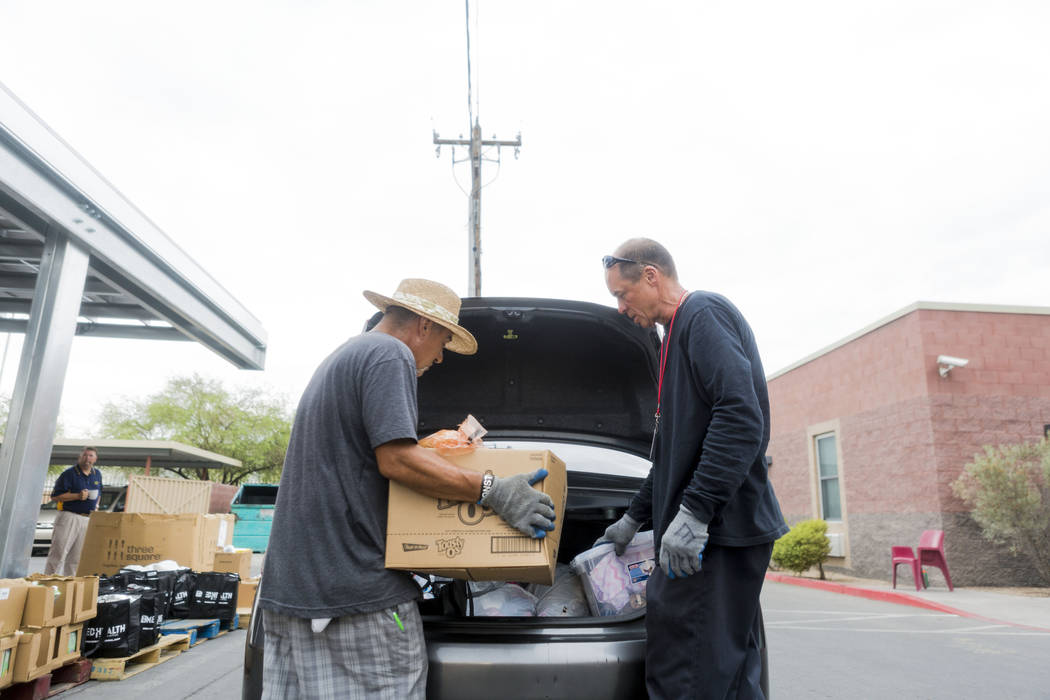 Work therapy participants Angelo Uribe, left, and Robert Edler load a car with food during the United States Department of Agriculture's food commodities distribution giveaway that occurs every ot ...