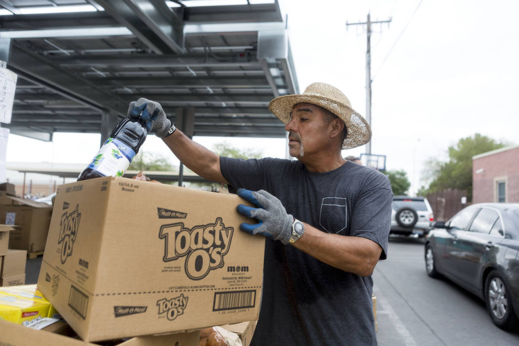 Work therapy participant Angelo Uribe helps with the United States Department of Agriculture's food commodities distribution giveaway that occurs every other month at the Las Vegas Rescue Mission  ...