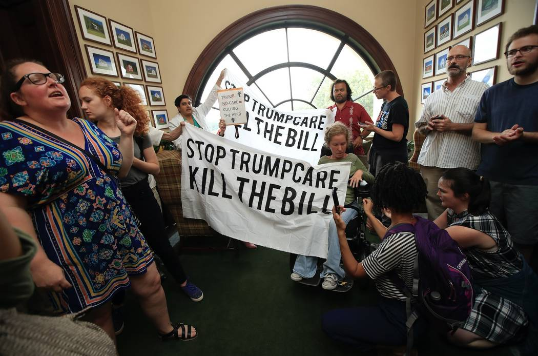 Protesters agains the Republican health care bill gather inside the office of Sen. Rob Portman, R-Ohio, on Capitol Hill in Washington, Monday, July 17, 2017.