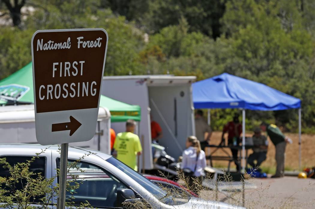First responders gather near the entrance to the First Crossing recreation area during the search and rescue operation for a victim in a flash flood along the banks of the East Verde River Monday, ...