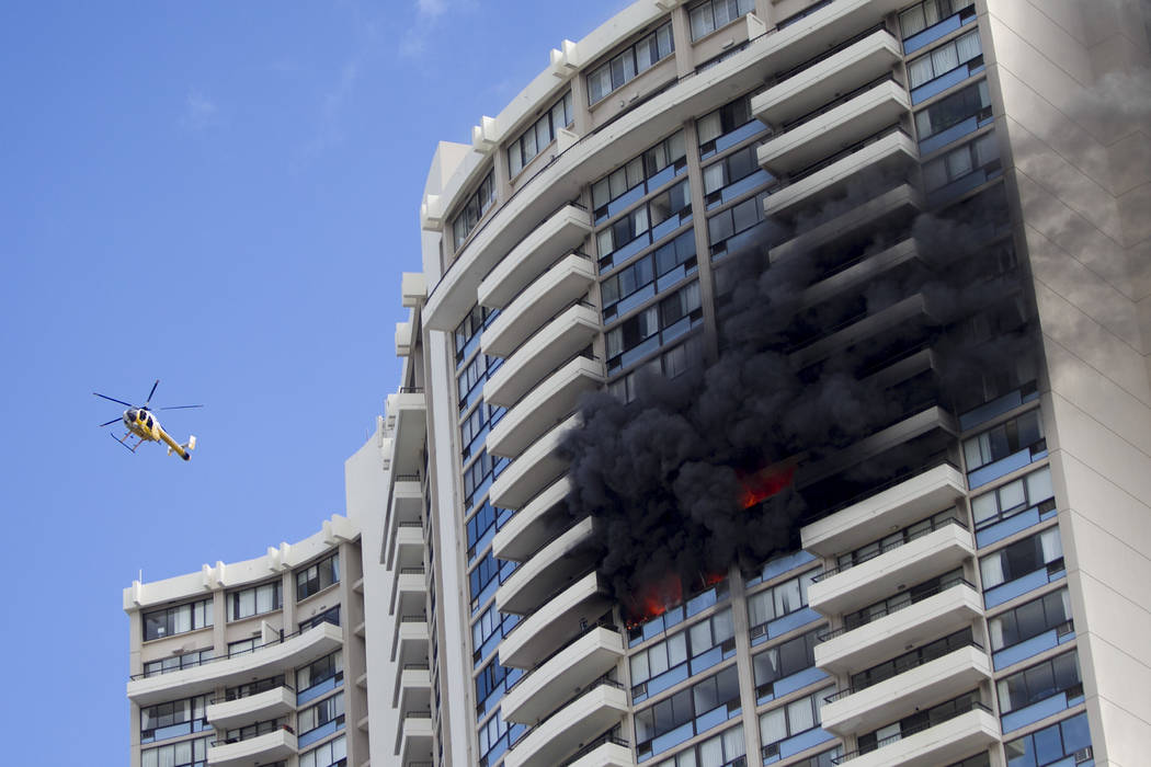 A Honolulu Fire Department helicopter flies near a fire burning on a floor at the Marco Polo apartment complex, Friday, July 14, 2017, in Honolulu. (Marco Garcia/AP)