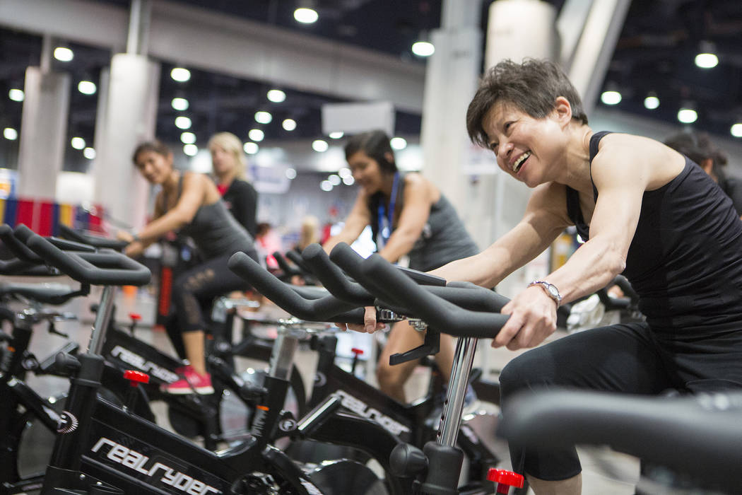 People attending the IDEA World Fitness & Nutrition Expo at the Las Vegas Convention Center follow a trainer while riding RealRyder bicycles, which tilt side-to-side to mimic on-road cycling.  ...