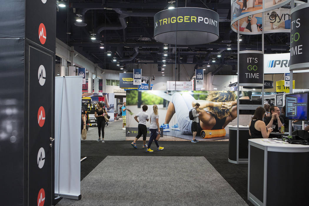 Attendees pass booths advertising workouts, fitness gear and other products during the IDEA World Fitness & Nutrition Expo at the Las Vegas Convention Center in Las Vegas on Thursday, July 20, ...