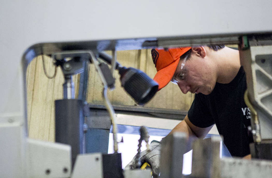 Frank Randell, a sheet metal apprentice, takes a measurement on a piece of metal at Young Electric Sign Company,YESCO, in southwest Las Vegas on Wednesday, July 19, 2017.  Patrick Connolly Las Veg ...