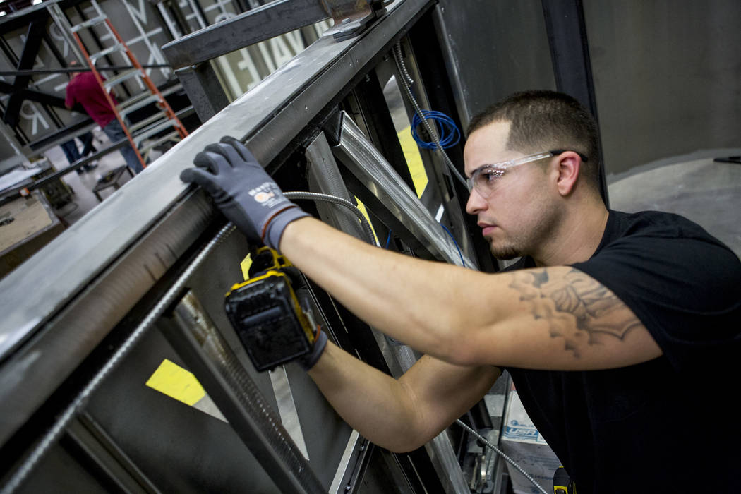 Rafael Andrade, an electrical apprentice, works on installing wiring brackets for a sign for Beverly Center mall in Los Angeles at Young Electric Sign Company, YESCO, in southwest Las Vegas on Wed ...