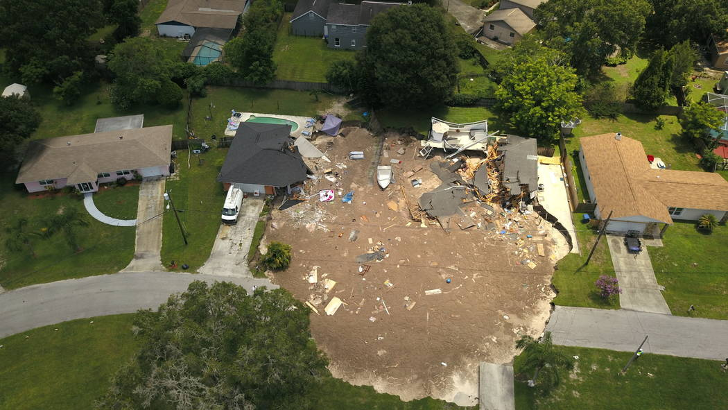 FILE-In this Friday, July 14, 2017 aerial file photo, debris is strewn about after a sinkhole damaged two homes in Land O' Lakes, Fla.  Heavy equipment will be brought in Wednesday, July 19, 2017  ...