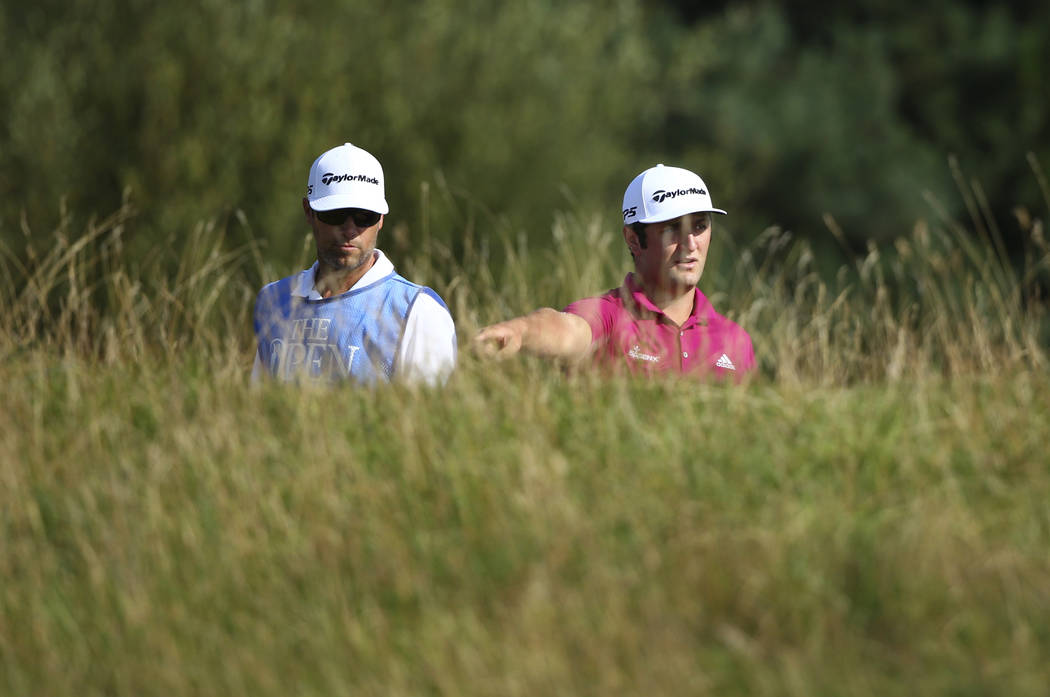 Spain's Jon Rahm, right, prepares to play from the rough on the 6th hole during a practice round ahead of the British Open Golf Championship, at Royal Birkdale, Southport, England Tuesday, July 18 ...