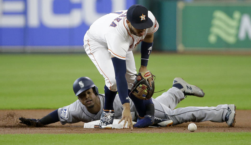 Seattle Mariners' Robinson Cano is safe at second base as Houston Astros' Carlos Correa reaches for the ball during the first inning of a baseball game Monday, July 17, 2017, in Houston. (Melissa  ...