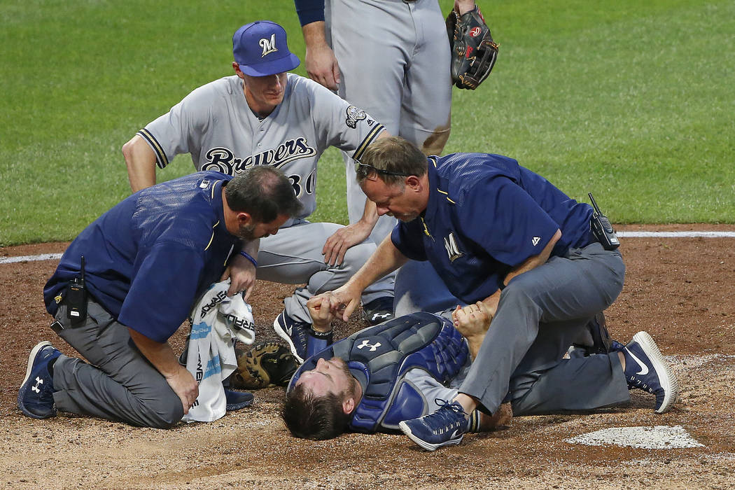 Gene J. Puskar/The Associate  Milwaukee Brewers manager Craig Counsell, top, watches as team trainers examine catcher Stephen Vogt, who was injured in a collision with Pittsburgh Pirates' Chad Kuh ...