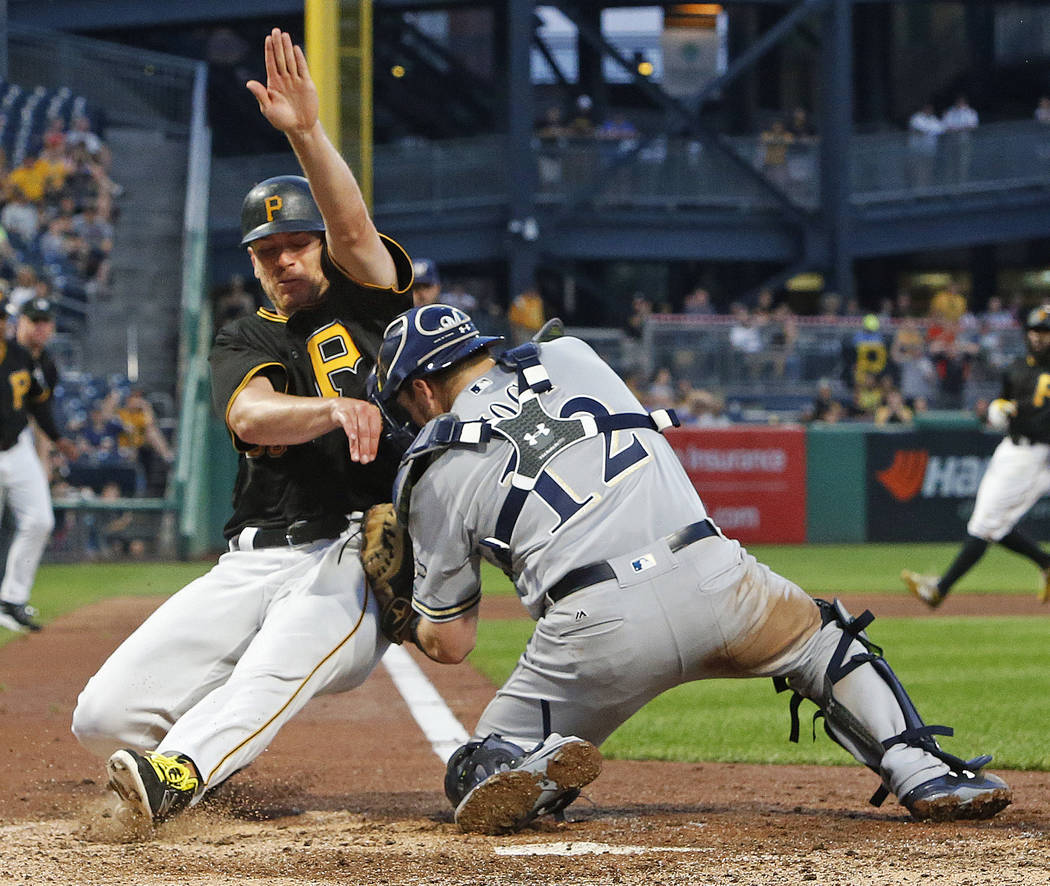 Pittsburgh Pirates' Chad Kuhl, left, collides with Milwaukee Brewers catcher Stephen Vogt while being tagged out during the fifth inning of a baseball game in Pittsburgh, Monday, July 17, 2017. Bo ...