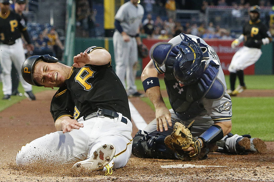 Pittsburgh Pirates' Chad Kuhl, left, reacts after a collision with Milwaukee Brewers catcher Stephen Vogt while being tagged out during the fifth inning of a baseball game in Pittsburgh, Monday, J ...