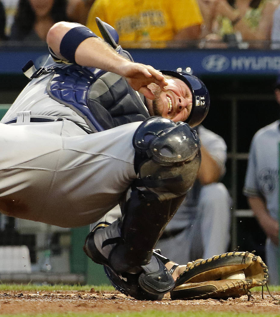 Milwaukee Brewers catcher Stephen Vogt grimaces as he falls to the ground after tagging out Pittsburgh Pirates' Chad Kuhl during the fifth inning of a baseball game in Pittsburgh, Monday, July 17, ...