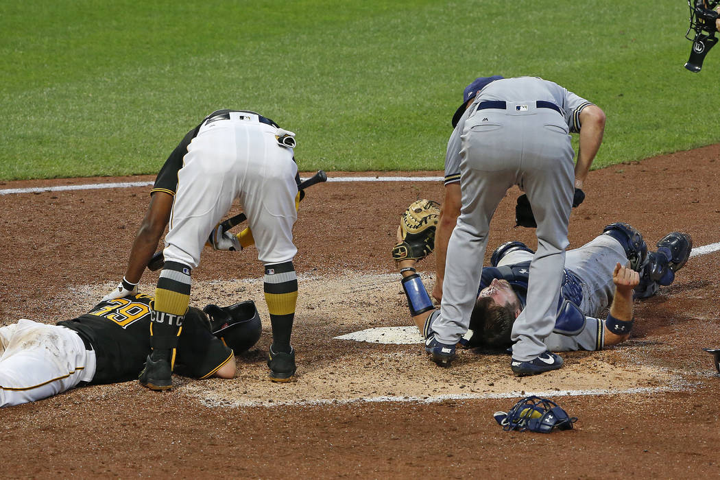 Pittsburgh Pirates' Chad Kuhl, left, and Milwaukee Brewers catcher Stephen Vogt, right, lie on the ground after a collision at home plate during the fifth inning of a baseball game in Pittsburgh,  ...