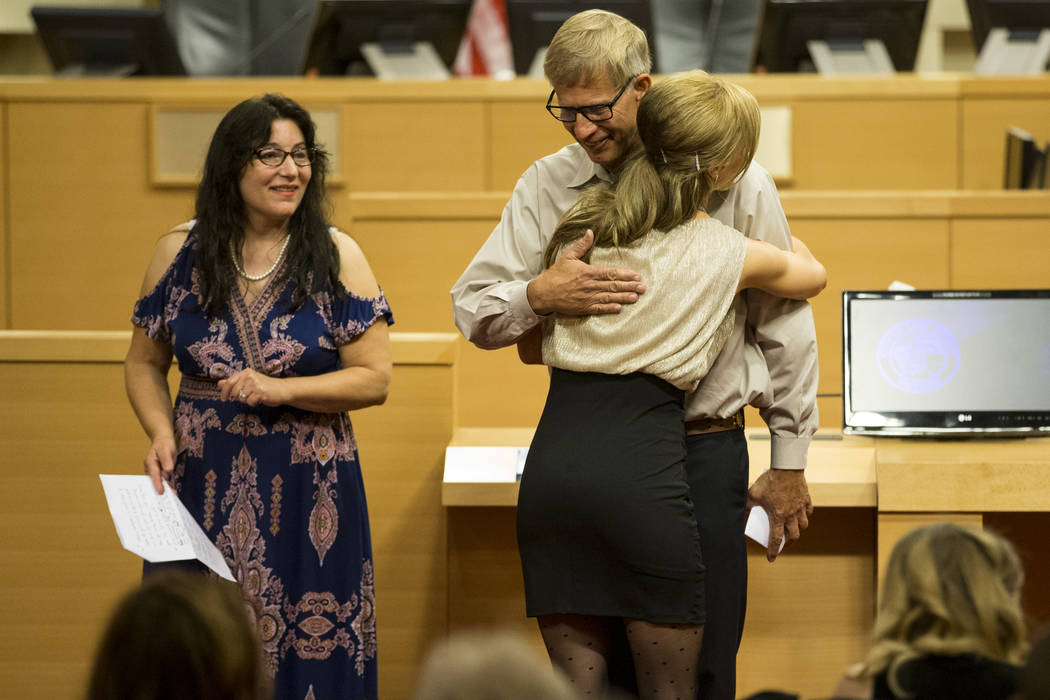 Diamond Jaskolski, left, looks on as her husband Mark hugs their daughter Stephanie graduating from the Youth Offender Court graduation at Las Vegas City Hall in Las Vegas, on Thursday, July 20, 2 ...