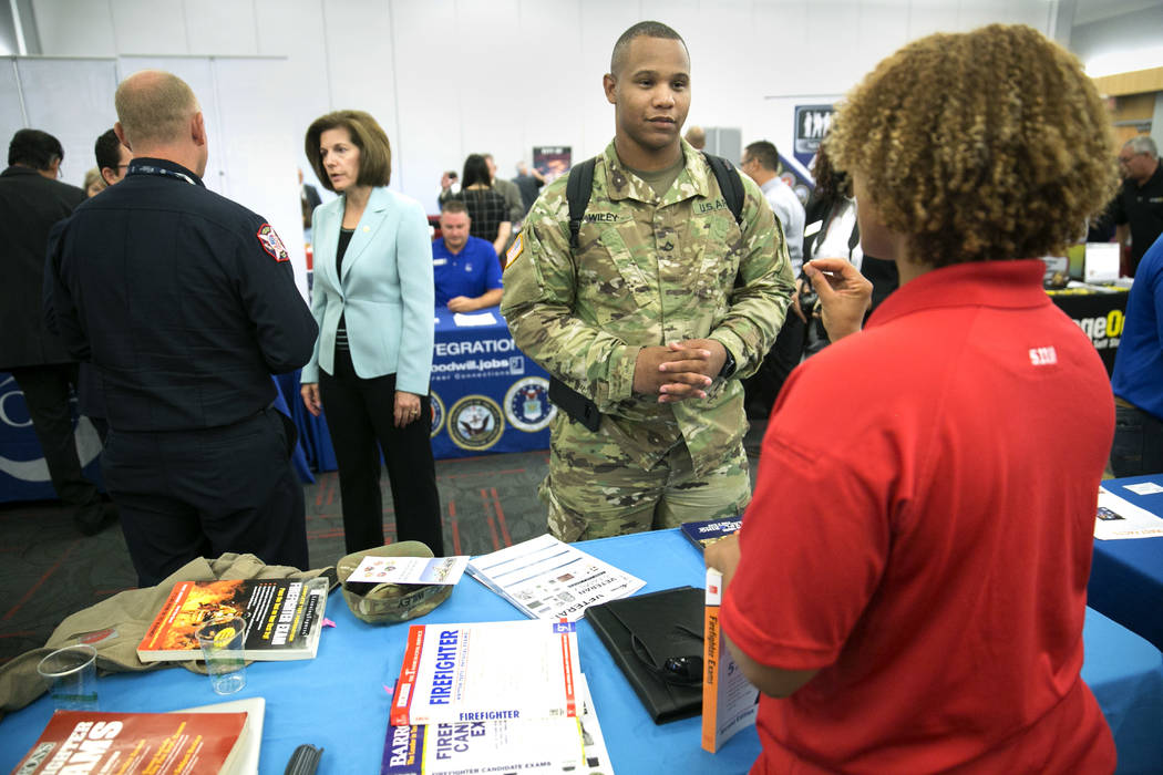 Eli Wiley speaks to Clark County firefighter Christa Fells about becoming a firefighter during a Veteran and Family Career Fair at UNLV in Las Vegas, Saturday, July 22, 2017, as Clark County Fire  ...