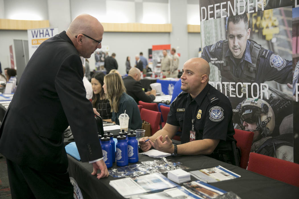 Willie Reuter, left, a Navy veteran, talks to U.S. Customs and Border Control Officer Michel Mirabal during a Veteran and Family Career Fair at UNLV in Las Vegas, Saturday, July 22, 2017.  Gabriel ...
