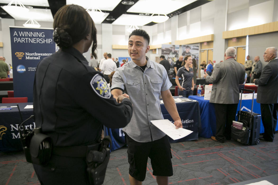 Jose Bravo shakes hands with Tracey Valenzuela of the Las Vegas Department of Public Safety during a Veteran and Family Career Fair at UNLV in Las Vegas, Saturday, July 22, 2017. Gabriella Angotti ...