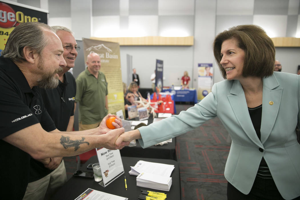 Greg Welsh, from left,  and Lee Preble, both air force veterans and representatives with Storage One, greet Sen. Catherine Cortez Masto during a Veteran and Family Career Fair at UNLV in Las Vegas ...