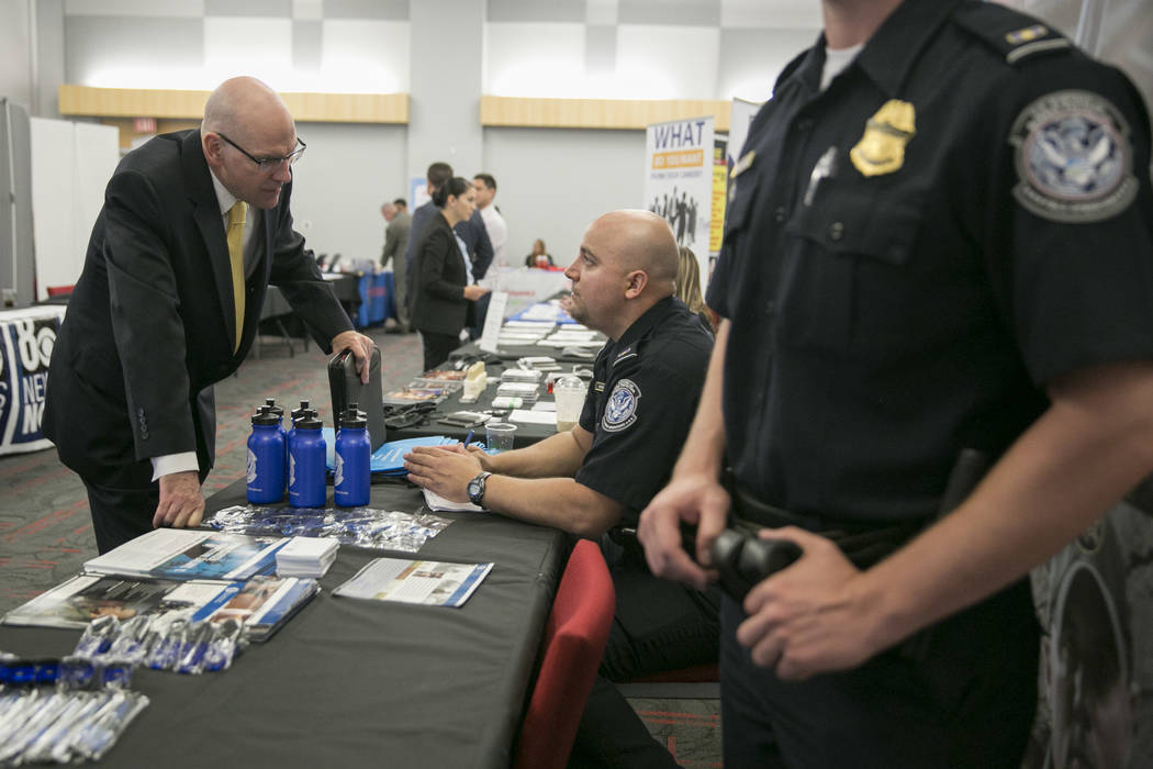 Willie Reuter,left, a Navy veteran, talks to U.S. Customs and Border Control Officer Michel Mirabal, center, during a Veteran and Family Career Fair at UNLV in Las Vegas, Saturday, July 22, 2017.  ...