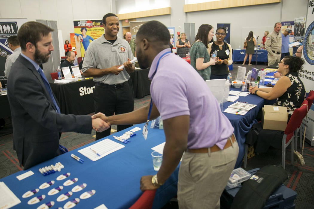Brad Sensibaugh, a U.S. Army veteran, shakes hands with Shontarius Webb of the Clark County School District while Patrick Brown looks on during a Veteran and Family Career Fair at UNLV in Las Vega ...