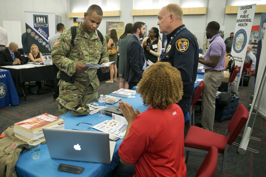Eli Wiley, left, speaks to Clark County firefighter Christa Fells and Clark County Fire Chief Greg Cassell during a Veteran and Family Career Fair at the University of Nevada, Las Vegas in Las Veg ...