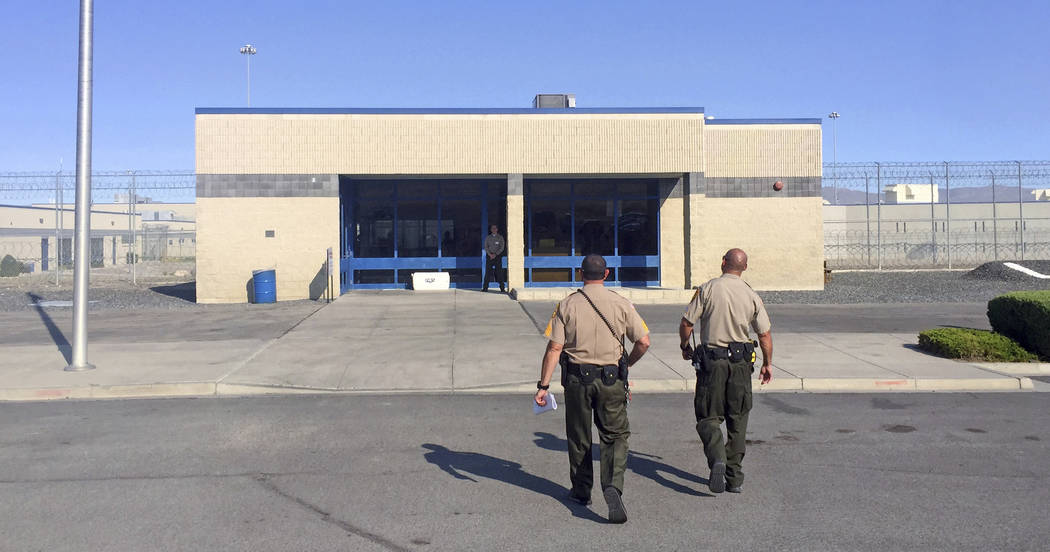 Officers walk toward the entrance to Nevada's Lovelock Correctional Center in Lovelock, Nev., where former NFL football star O.J. Simpson is being held Thursday, July 20, 2017. Simpson is making t ...