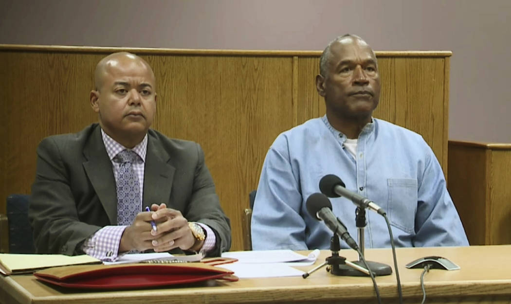 Former NFL football star O.J. Simpson appears with his attorney, Malcolm LaVergne, left, via video for his parole hearing at the Lovelock Correctional Center in Lovelock, Nev., on Thursday, July 2 ...