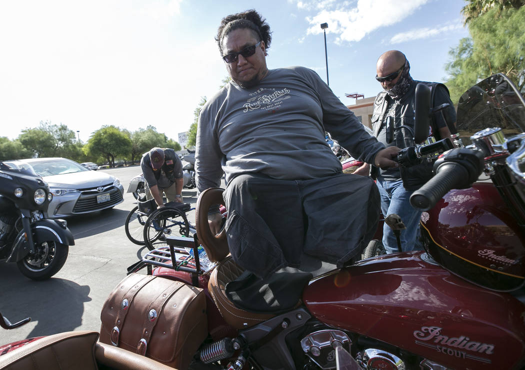 Retired Army Cpl. Joshua Stein, a double amputee who lost his legs during an explosion in Iraq, mounts his modified Indian Scout Avenger at the Veterans Memorial outside the Sawyer Building, Satur ...