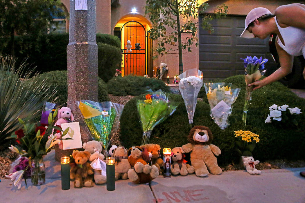 A woman leaves a flower bouquet at a makeshift memorial on the 10300 block of Numaga Road in Las Vegas on July 11, 2017, during a vigil for the three family members who died in a murder-suicide. ( ...