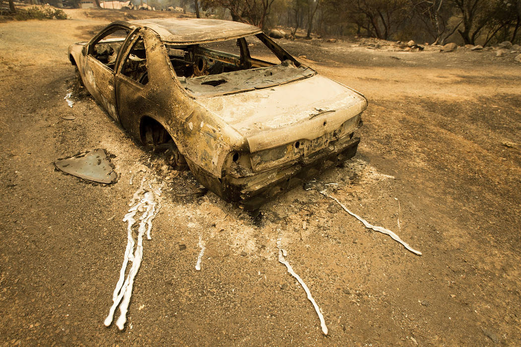 A scorched car rests next to a residence leveled by the Detwiler fire near Mariposa Calif. on Wednesday