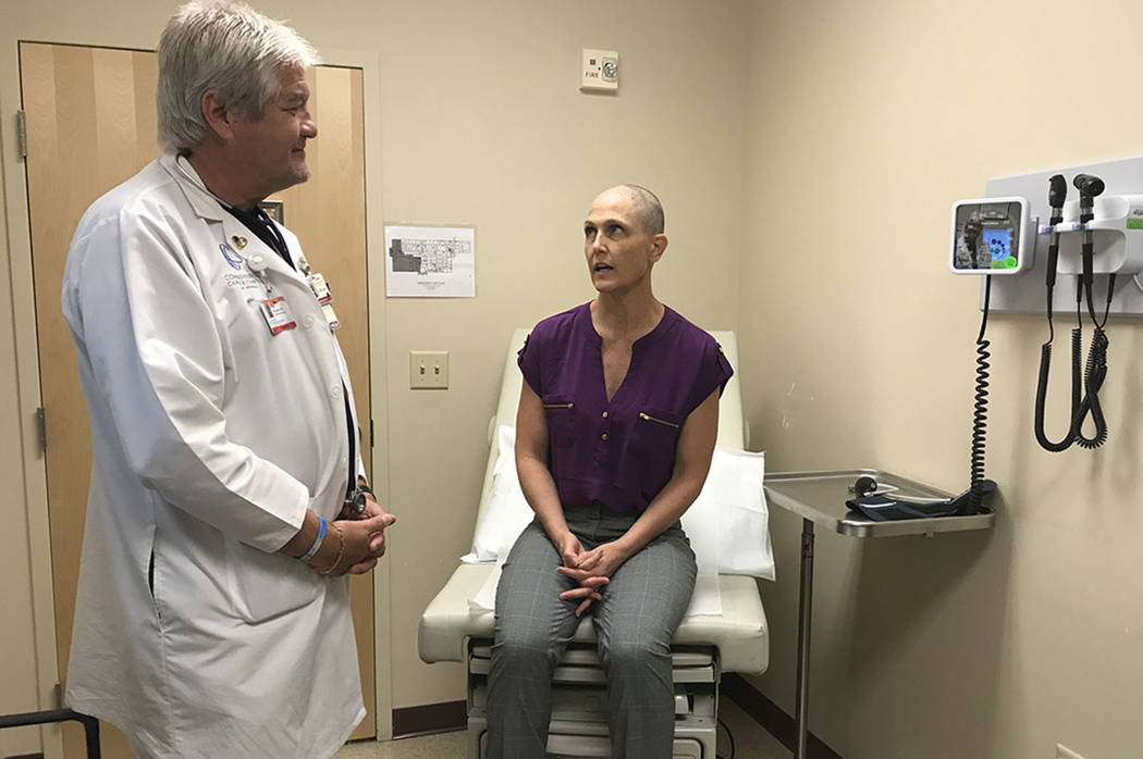 Comprehensive Cancer Centers of Nevada oncologist Dr. Paul Michael examines Las Vegas paramedic Tricia Klein, who three years ago was diagnosed with an aggressive brain tumor similar that of Arizo ...