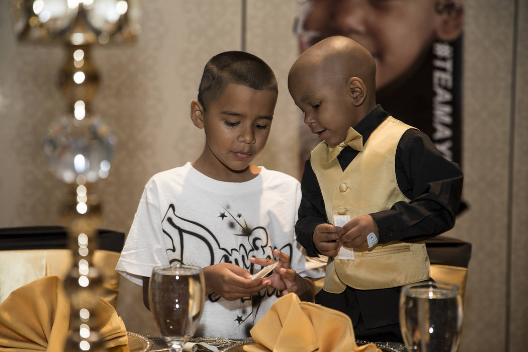 Davian Huerta, left, with his cousin Ayden Brown, 2, who was diagnosed with terminal cancer at the age of one, during a fundraiser for Brown by his family at the Suncoast on Saturday, July 22, 201 ...