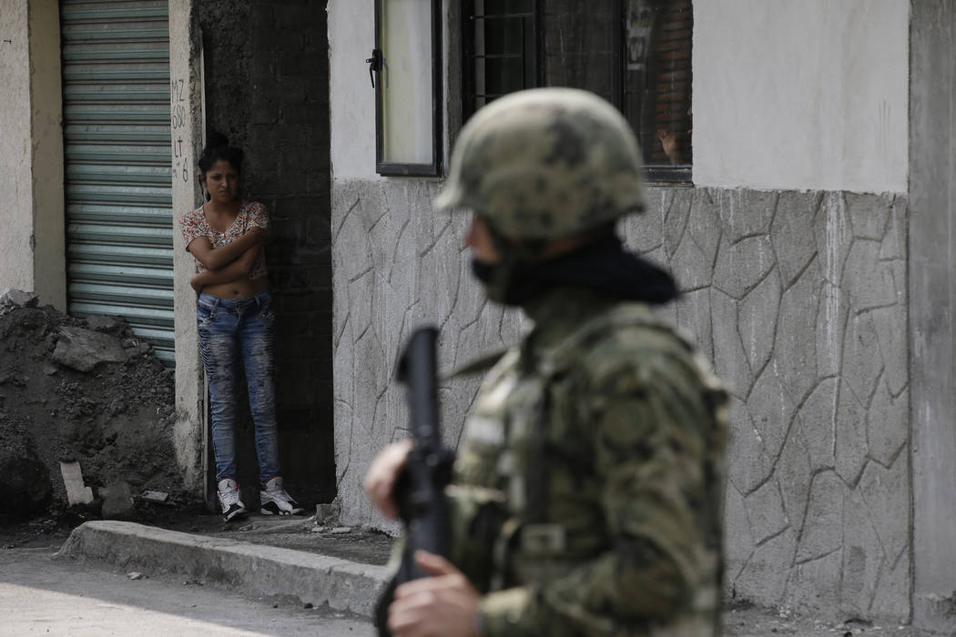 A woman peers out from a home as Marines block off the area where the suspected leader of a drug gang and seven others were killed, according to the Navy, in southern Mexico City, Thursday, July 2 ...