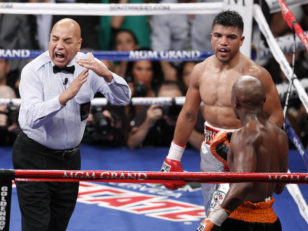 Referee Joe Cortez calls time after Victor Ortiz, top right, head butted Floyd Mayweather in the fourth round during a WBC welterweight title fight, Saturday, Sept. 17, 2011, in Las Vegas. Mayweat ...