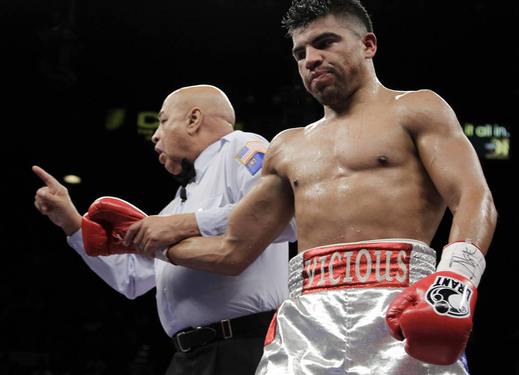 Victor Ortiz, right, has a point taken from him by referee Joe Cortez after a head butt on Floyd Mayweather Jr. during their WBC welterweight title fight Saturday, Sept. 17, 2011, in Las Vegas. Ma ...