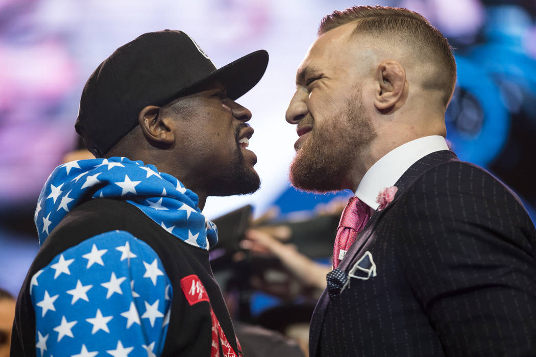 Boxer Floyd Mayweather Jr., left, and UFC fighter Conor McGregor during a press conference in their world boxing tour to promote their upcoming fight, at Staples Center in Los Angeles on Tuesday,  ...