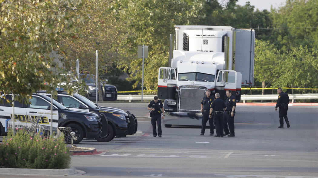 San Antonio police officers investigate the scene Sunday, July 23, 2017, where eight people were found dead in a tractor-trailer loaded with at least 30 others outside a Walmart store in stifling  ...