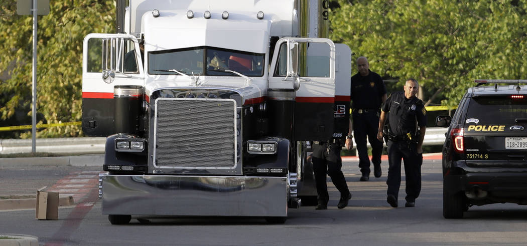 San Antonio police officers investigate the scene where eight people were found dead in a tractor-trailer loaded with at least 30 others outside a Walmart store in stifling summer heat in what pol ...