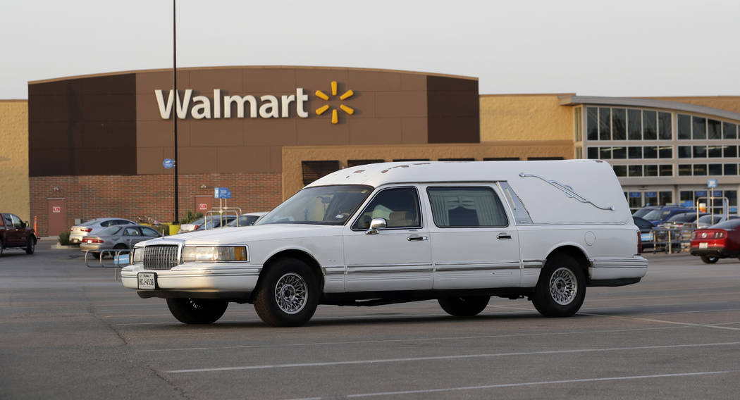 A hearse sits in the parking lot of a Walmart store where eight people were found dead in a tractor-trailer loaded with at least 30 others outside in stifling summer heat in what police are callin ...