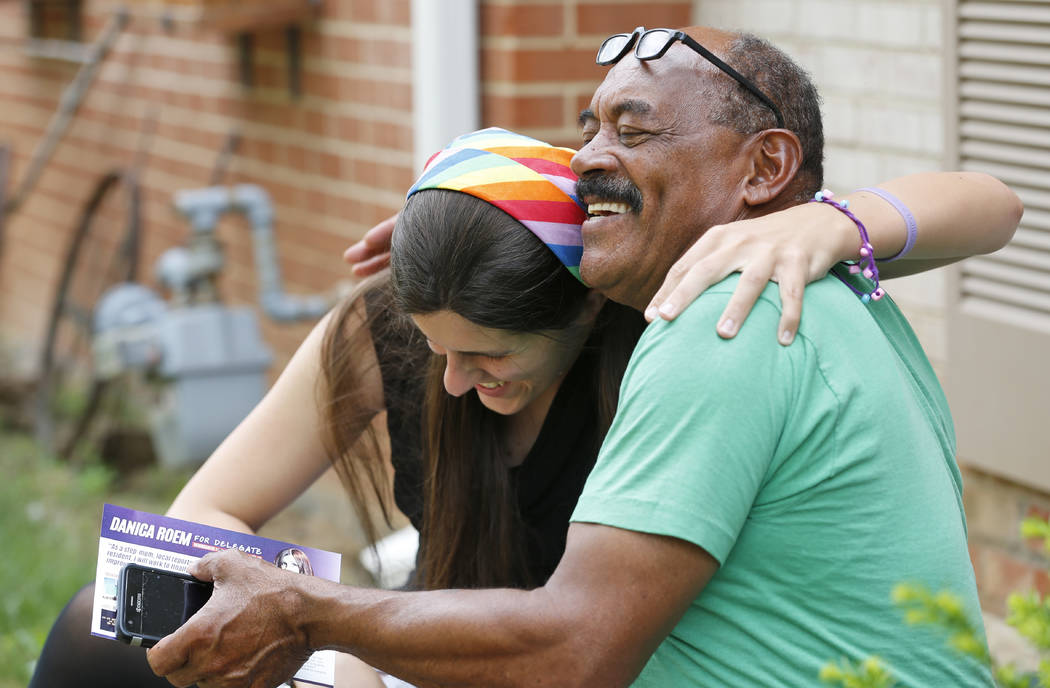 Democratic nominee for the House of Delegates 13th district seat, Danica Roem, gets a hug from supporter and local resident, Godfrey Wade, as she canvasses a neighborhood Wednesday, June 21, 2017, ...
