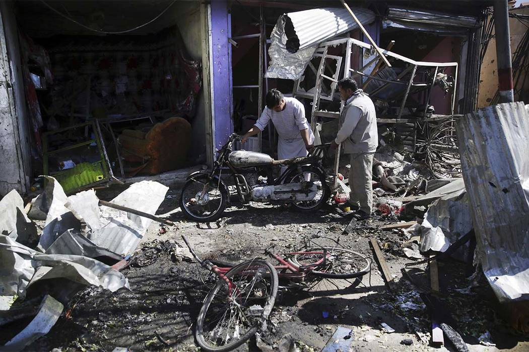 Men look at the remains of their properties at the site of a suicide attack in Kabul, Afghanistan, Monday, July 24, 2017. A suicide car bomb killed dozens of people as well as the bomber early Mon ...