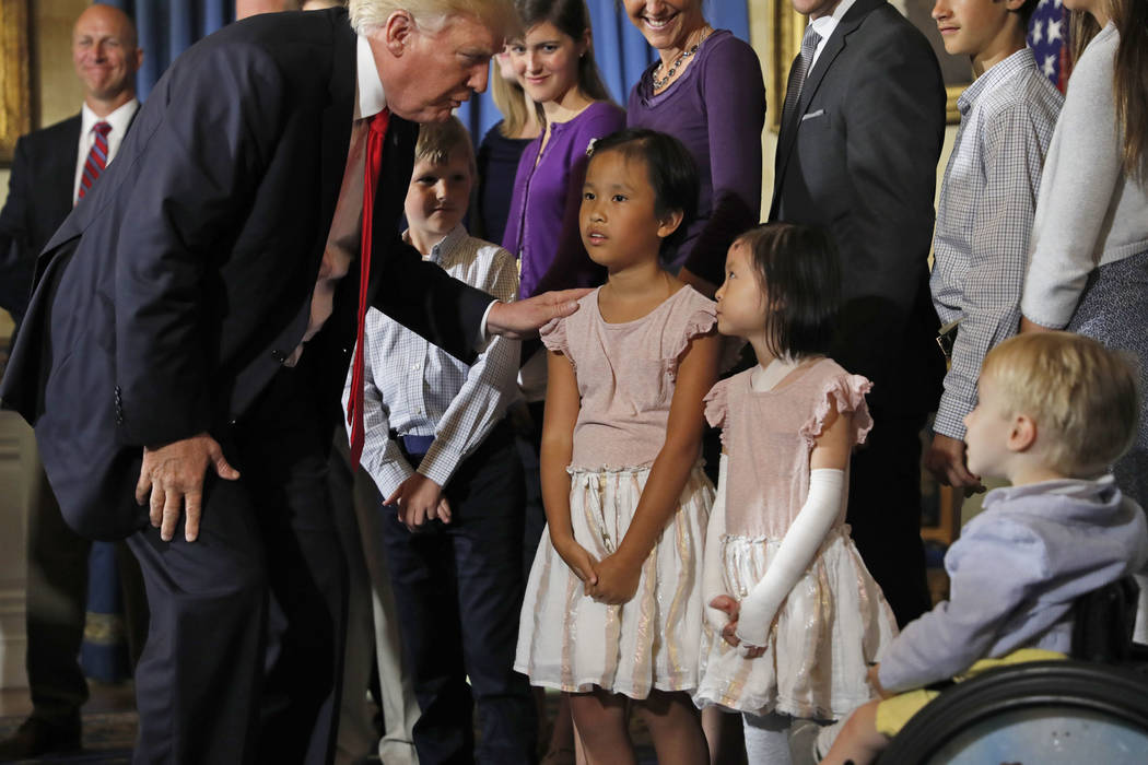 President Donald Trump greets families that oppose Obamacare during an event about healthcare, Monday, July 24, 2017, in the Blue Room of the White House in Washington. (AP Photo/Alex Brandon)